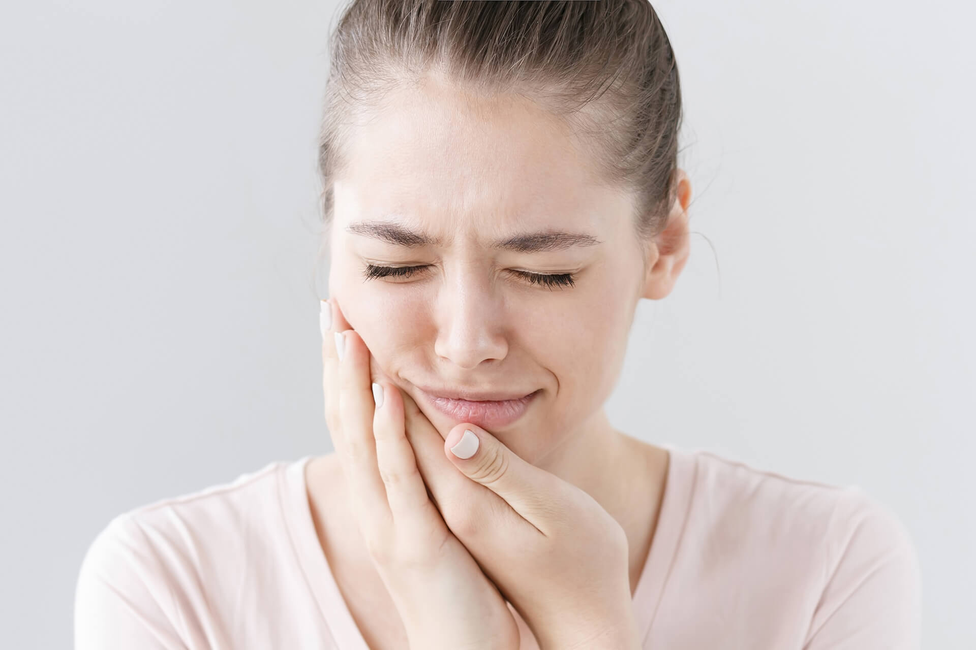 girl holding jaw in pain